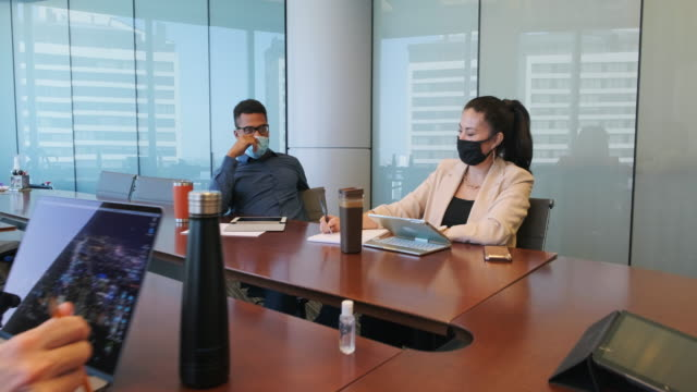 diverse business team in a meeting wearing protective face masks - board room stock videos & royalty-free footage