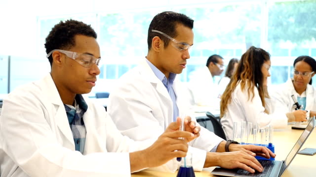 diverse chemists or chemistry students work on scientific experiment - becher video stock e b–roll