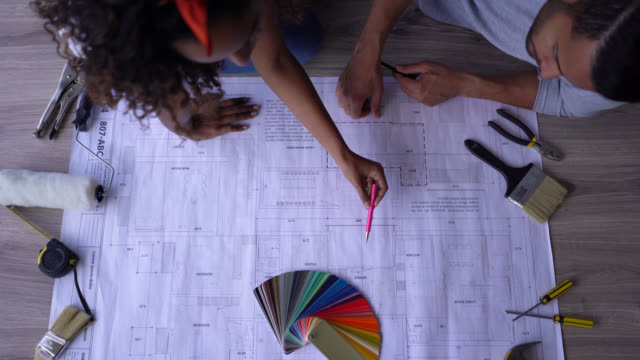 diverse couple discussing diy projects at their new home while looking at a blueprint sitting on floor - colour sample stock videos & royalty-free footage