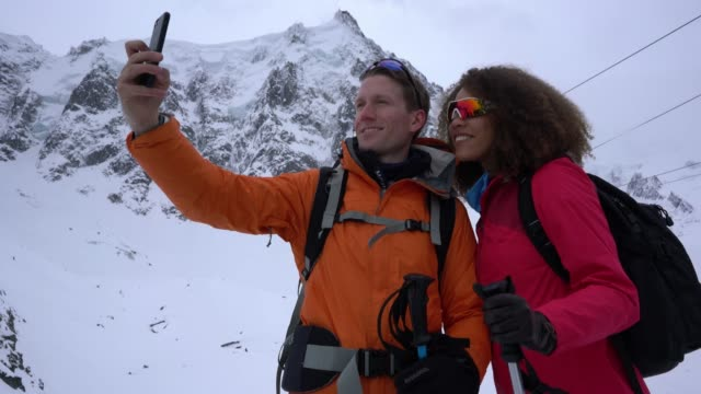 diverse couple hiking the alps during winter taking a selfie with smartphone smiling - ethnicity stock videos & royalty-free footage