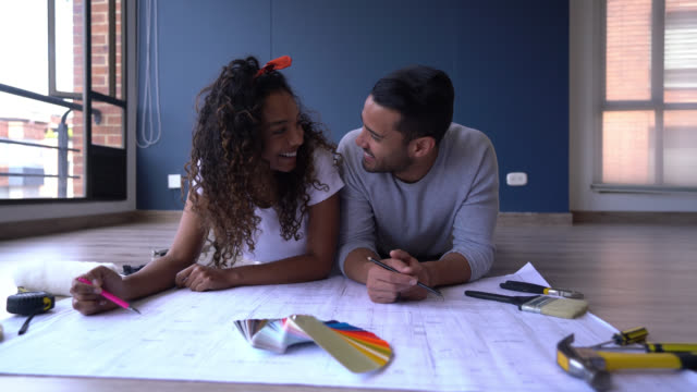 diverse couple lying down on floor looking at the blueprint of their new home planning very excited - tape measure stock videos & royalty-free footage