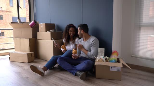 olika par tar en paus efter att flytta lådor till sitt nya hem äta croissanter och titta på något på tablett - flyttlåda bildbanksvideor och videomaterial från bakom kulisserna