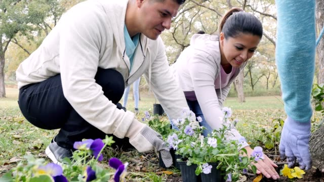 Diverse couple volunteer with neighbors during community beautification day