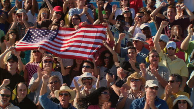 ha ws diverse crowd cheering and holding american flag in bleachers / homestead, fl, usa - american flag stock videos and b-roll footage