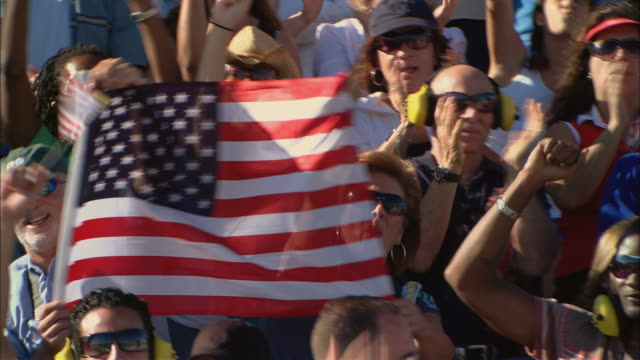 HA MS PAN Diverse crowd cheering and waving American flags in bleachers / Homestead, FL, USA