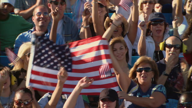 vídeos de stock e filmes b-roll de ha ms diverse crowd cheering and waving american flags, then stands up in bleachers / homestead, fl, usa - patriotismo