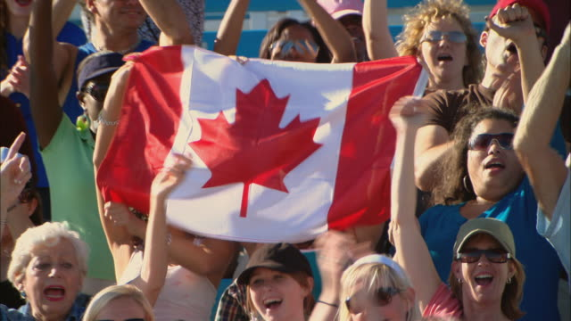 HA MS Diverse crowd cheering and waving Canadian flag, then stands up in bleachers / Homestead, FL, USA