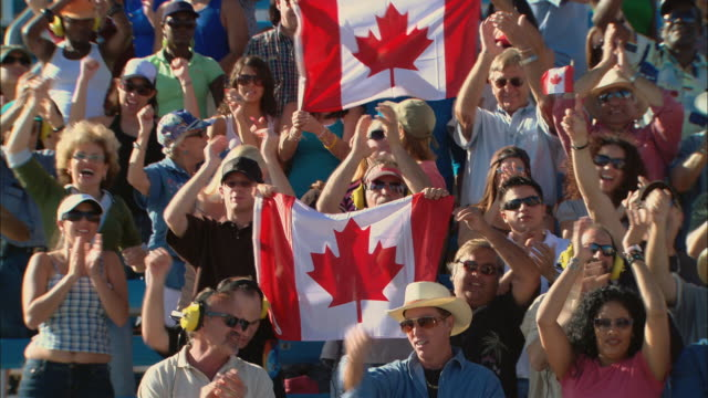 ha ms pan diverse crowd cheering and waving canadian flags in bleachers / homestead, fl, usa - kanadische flagge stock-videos und b-roll-filmmaterial