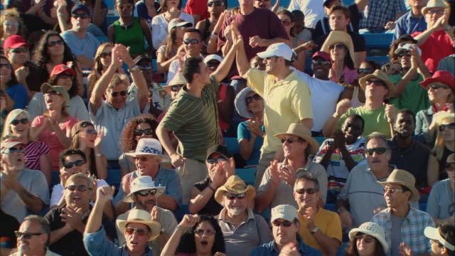 HA WS Diverse crowd clapping while two men stand up and high-five in bleachers / Homestead, FL, USA