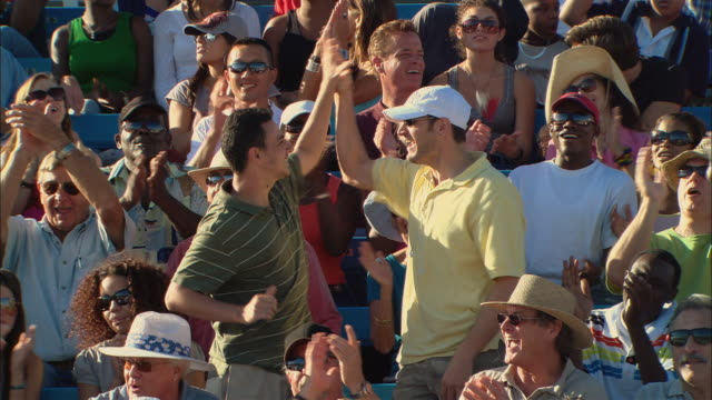 HA MS Diverse crowd clapping while two men stand up and high-five in bleachers / Homestead, FL, USA