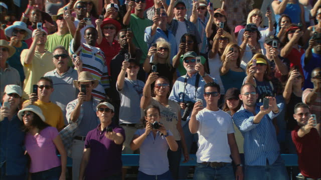 ha ws pan diverse crowd standing up and taking photos with cell phones in bleachers / homestead, fl, usa - see other clips from this shoot 15 stock videos and b-roll footage