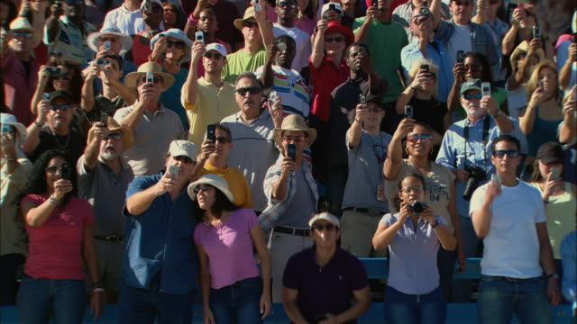 HA WS Diverse crowd standing up and taking photos with cell phones, then sits down in bleachers / Homestead, FL, USA