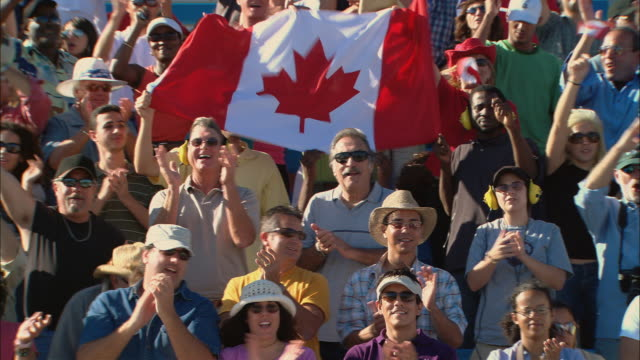 ha ms pan diverse crowd standing up and waving canadian flags in bleachers / homestead, fl, usa - bandiera del canada video stock e b–roll