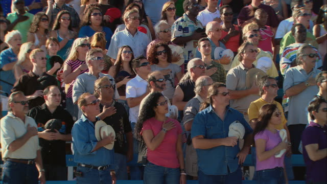 vídeos de stock, filmes e b-roll de ha ws diverse crowd standing up, removing hats, and placing hands over hearts during national anthem / homestead, fl, usa - ficando de pé