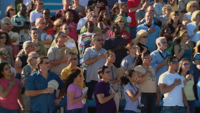ha ws diverse crowd standing with hands over hearts during national anthem / homestead, fl, usa - hand aufs herz stock-videos und b-roll-filmmaterial