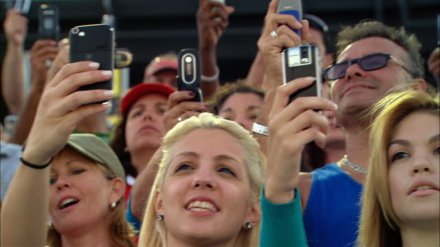 vídeos y material grabado en eventos de stock de la cu pan diverse crowd taking photos with cell phones in bleachers / homestead, fl, usa - multi ethnic group