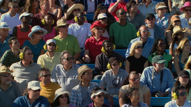 ha ms pan diverse crowd watching and wearing ear protectors in bleachers / homestead, fl, usa - ear protectors stock videos and b-roll footage