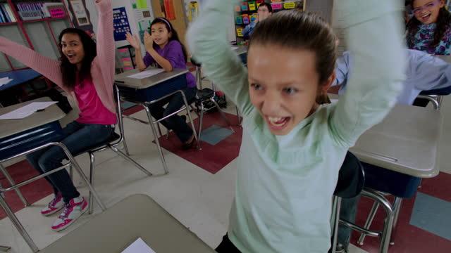 vídeos de stock, filmes e b-roll de diverse elementary students cheer and celebrate at their desks during class. - sala de aula