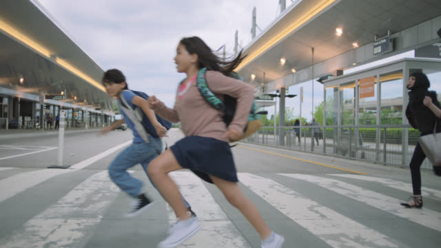 stockvideo's en b-roll-footage met diverse family runs through crosswalk outside airport at ground transportation. - druk spanning