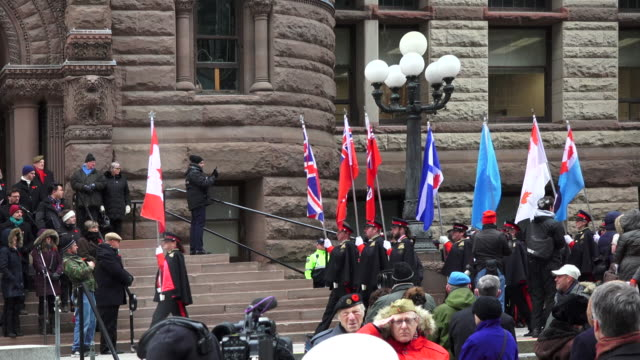 diverse flags and military music band arrive at the old city hall where the ceremony for remembrance day is held - armistice day stock videos and b-roll footage