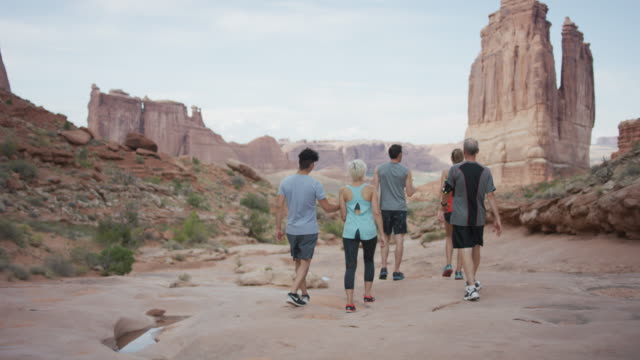 heterogene gruppe wandern in utah - moab utah stock-videos und b-roll-filmmaterial
