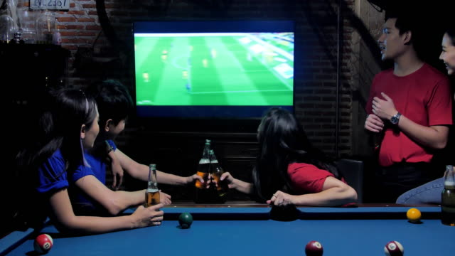 diverse group of asian friends watches tv in the sporstbar.their team scores the goal and wins.excited friends watching soccer match while having beer in bar.they all cheer when their favourite team scores.young people cheer. - glee tv show stock videos and b-roll footage