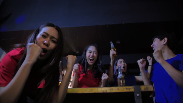 diverse group of asian friends watches tv in the sporstbar.their team scores the goal and wins.excited friends watching soccer match while having beer in bar.they all cheer when their favourite team scores.young people cheer. - contest stock videos & royalty-free footage