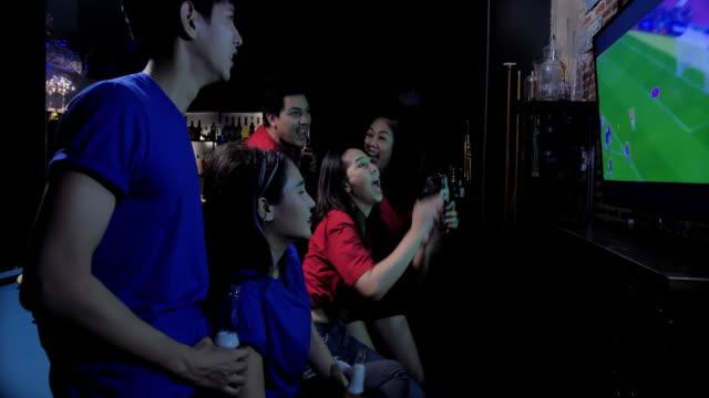 vídeos y material grabado en eventos de stock de diverso grupo de amigos asiáticos relojes de televisión en el bar de deportes. su equipo anota el gol y gana. amigos emocionados viendo partido de fútbol mientras que la cerveza en el bar. todos animan cuando su equipo favorito anota. animadoras jóvene - barra futbol