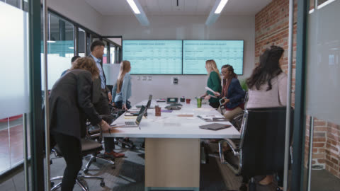 diverse group of business colleagues stand up to exit as they finish a meeting in an office conference room - the end stock videos & royalty-free footage
