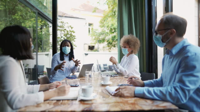 diverse group of business people having a meeting at the coffee shop while wearing protective masks during the coronavirus pandemic - brainstorming stock videos & royalty-free footage