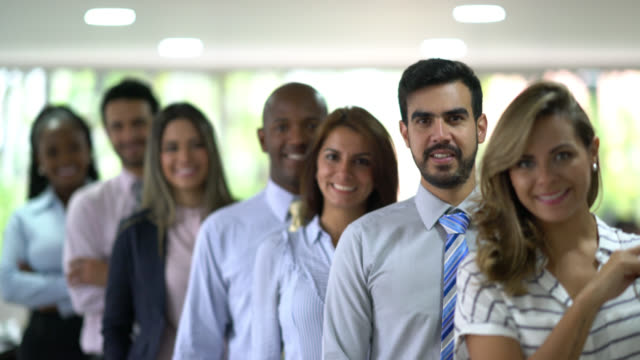 diverse group of business people standing in a line behind all looking at the camera smiling - arms crossed stock videos & royalty-free footage