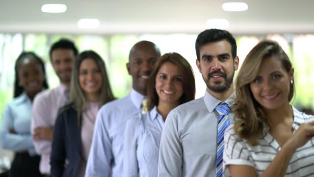 stockvideo's en b-roll-footage met diverse groep van mensen uit het bedrijfsleven staan in een lijn achter al kijken naar de camera glimlachen - armen over elkaar