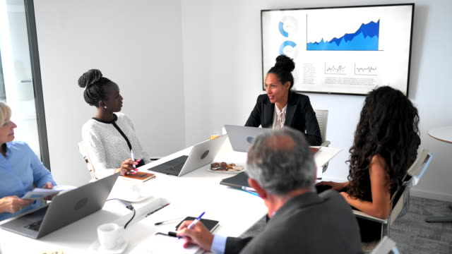diverse group of businesspeople sitting at conference table - diversity stock videos & royalty-free footage
