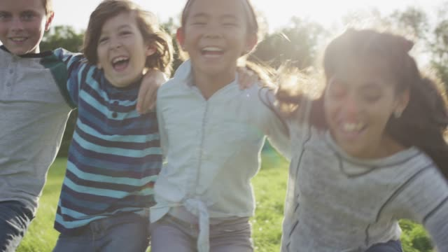 Diverse group of children embracing before falling into the grass