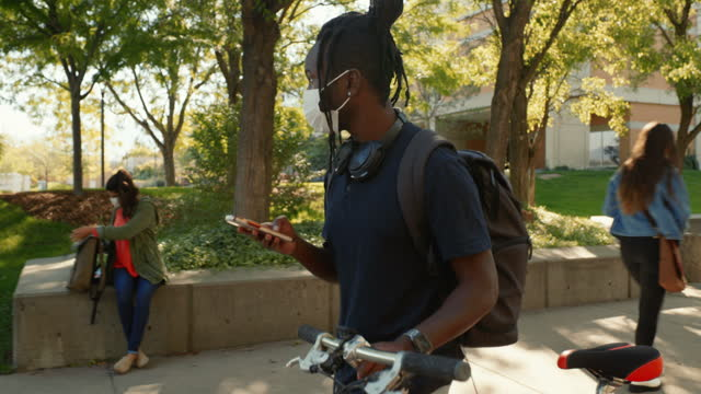 vídeos de stock, filmes e b-roll de diversos grupos de estudantes universitários no campus usando uma máscara facial para proteção. - universidade comunitária