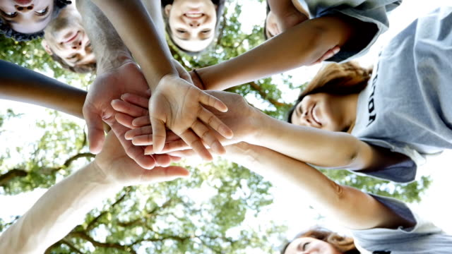diverse group of community volunteers with hands in a huddle outdoors - a helping hand stock videos & royalty-free footage