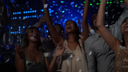Diverse group of couples dancing at a bar shouting excited as confetti drops