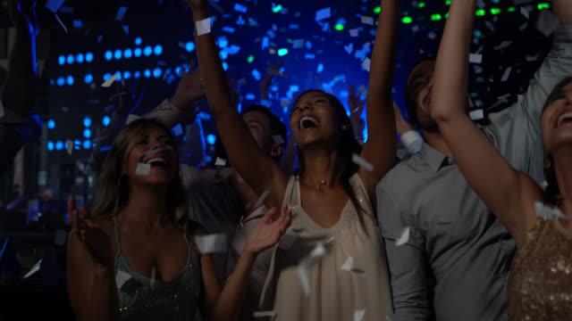 vidéos et rushes de groupe divers de couples dansant à un bar criant excité pendant que les baisses de confettis - boîte