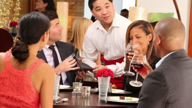 Diverse group of couples in restaurant.