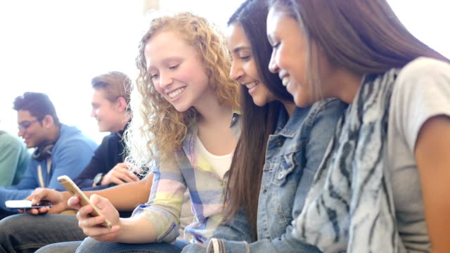 diverse group of cute high school students looking at smart phone together - endast tonåringar bildbanksvideor och videomaterial från bakom kulisserna
