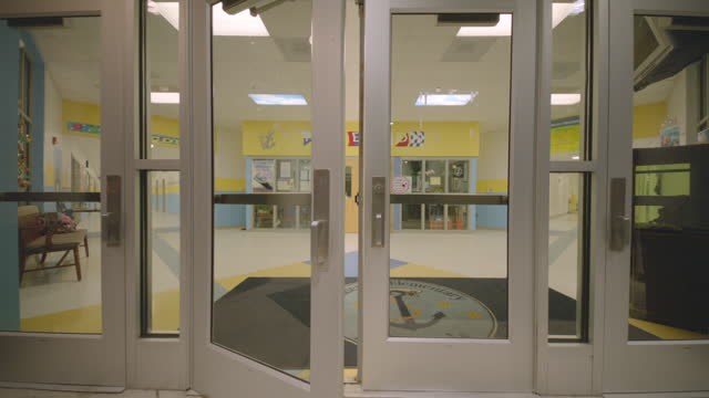 Students bust through school doors (slow motion)