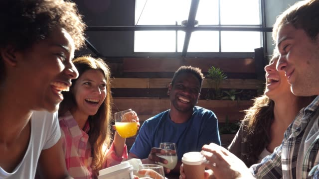 Diverse group of friends at a restaurant enjoying drinks and coffee while talking and laughing