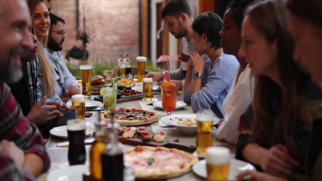 diverse group of friends eating outdoors in pub - lunch stock videos & royalty-free footage