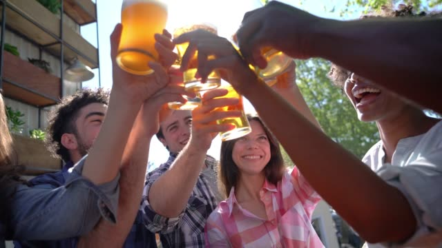 vídeos de stock e filmes b-roll de diverse group of friends enjoying happy hour at an outdoor bar and making a toast very happy - beer alcohol