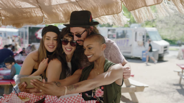 diverse group of friends pose for smartphone selfie at picnic table with food truck in background. - beatnik stock videos & royalty-free footage