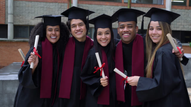 diverse group of friends smiling at camera celebrating after their graduation ceremony - diploma video stock e b–roll