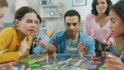 Diverse Group of Guys and Girls Playing in a Strategic Uniquely Designed Board Game with Cards and Dice. Friends Having Fun Reading Cards, Joking, Moving Figures and Laughing in a Cozy Living Room