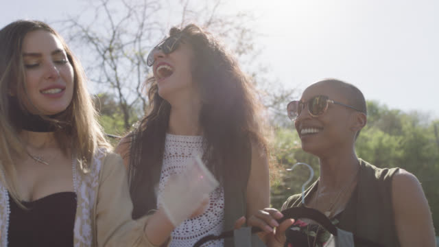vídeos de stock e filmes b-roll de a diverse group of happy bohemian women are laughing at a polaroid they took while trying on boho clothing from a mobile fashion truck - calçada