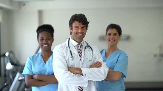 Diverse group of healthcare professionals at a physical recovery clinic looking at camera smiling