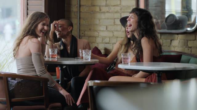 diverse group of hip young women sit and talk over drinks in austin cocktail bar at happy hour. - bar video stock e b–roll